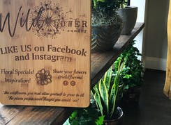 Posed with the potted plants, a wooden sign encourages visitors like us on Facebook and Instagram